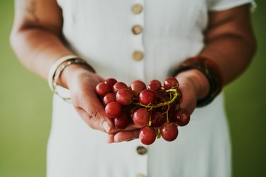 Black person assigned female at birth in white dress holding bunch of red grapes