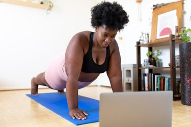 Woman exercising at home following a fitness video online