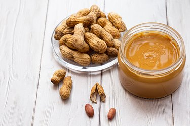 A jar of peanut butter with a bunch of peanuts on a white wooden table. Homemade peanut butter, natural, healthy food. The modern wellness and vegan concept.