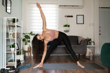 young female woman practicing a Hatha yoga triangle pose in her living room