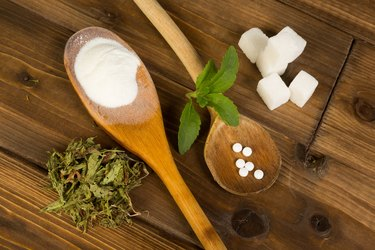 Sugar and stevia in wooden spoons on wooden table