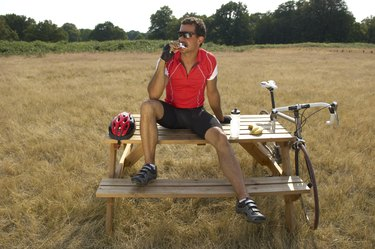 Male cyclist sitting on picnic table, eating