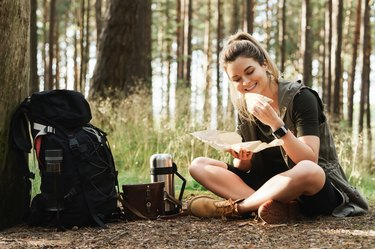 Female hiker during small halt eating sandwich in green forest
