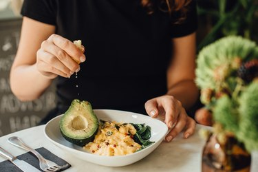 Midsection of woman eating scrambled eggs and avocado for breakfast