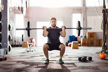 Man doing a barbell squat in a gym with dumbbells behind him