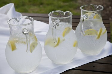 Three pitchers of ice water with lemon slices on white napkin