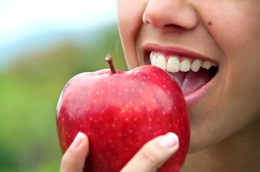 A woman eating an apple high in quercetin, as a natural remedy for allergies
