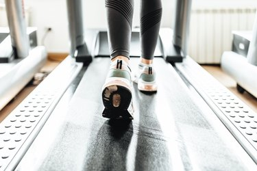 close up of a woman's sneakers running on treadmill