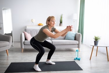 middle-aged woman doing squats on a black yoga mat in living room