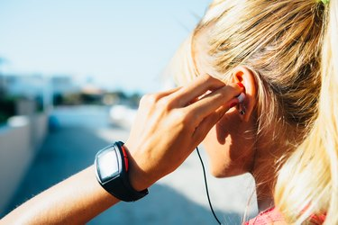 woman putting on headphones before her outdoor workout