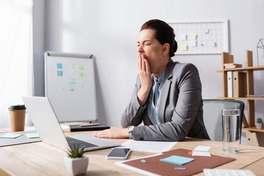 Sleepy businesswoman with hand near mouth yawning while sitting at workplace in office