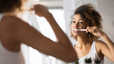girl brushing her teeth in the morning after breakfast