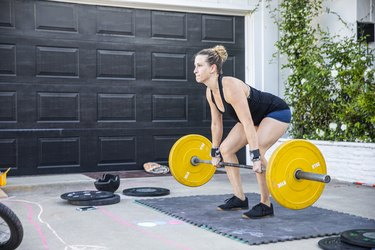 Woman doing deadlifts with barbell at home.