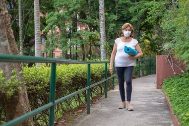 Woman walking outside to yoga class wearing face mask carrying blue mat outside