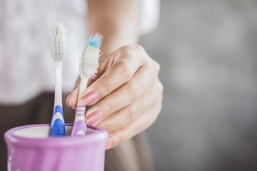 close view of a woman's hand using an old toothbrush