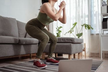 Woman performing squat exercise doing lower-body workout video at home