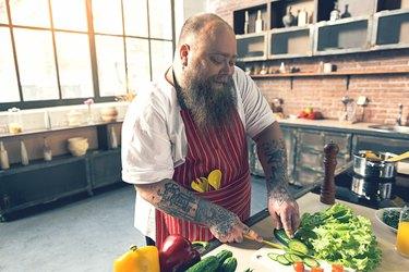 Happy male chef preparing healthy salad