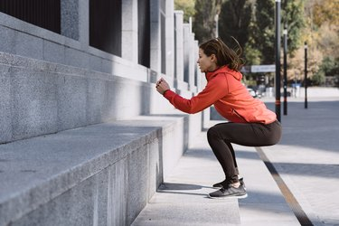 young adult sporty woman doing a squat jump, a glute combination exercise on a concrete staircase outside