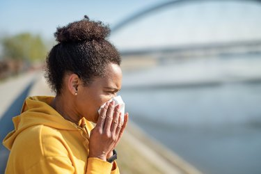 black woman wearing a yellow hoodie sneezing and blowing nose into a tissue while exercising outdoors