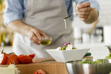 Man pouring olive oil on salad, as an example of daily habits for healthy aging