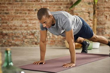 Young Male Athlete Practicing Push-Ups At Home