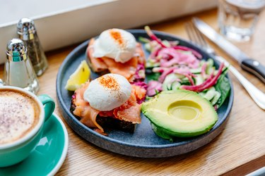 Poached eggs with salmon and avocado on the plate, side view