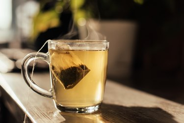 glass mug of hot water with tea bag steeping on wooden counter