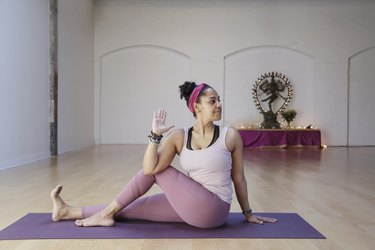 Woman with curly dark hair, sits in a seated spinal twist on an eco-friendly yoga mat, with a Hindu god sculpture in the background of a yoga studio.