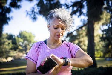 Senior Black Woman Running with a Fitness Tracker