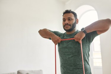 Work out indoors. Cropped shot of young active man looking away, exercising with resistance band during morning workout at home. Sport, healthy lifestyle