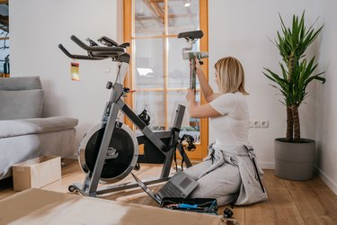 Woman assembling stationary bicycle in living room for at home cardio machine workout