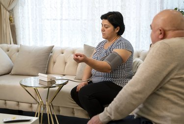 Senior woman sits on a couch and measures her blood pressure at home to see if it is the average blood pressure for a woman