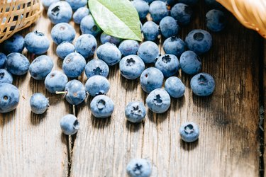 Polyphenol-rich blueberries scattered on a rustic wooden table. Juicy and fresh blueberries with green leaves. The concept for healthy eating and nutrition.