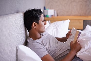 Man reading a book in bed to calm racing thoughts at night