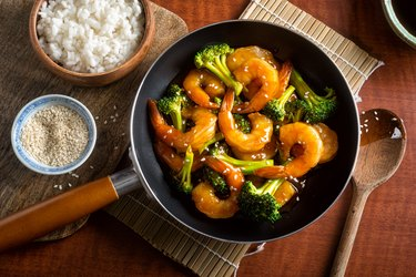 Shrimp and broccoli in pan with white rice on the side