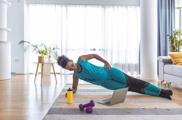woman doing a side plank exercise with purple dumbbells in her living room