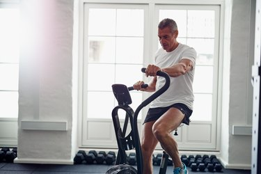 Mature man riding a health club stationary bike for exercise after total knee replacement