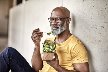 Man having lunch break eating a salad with nitrate-rich leafy greens for muscle building