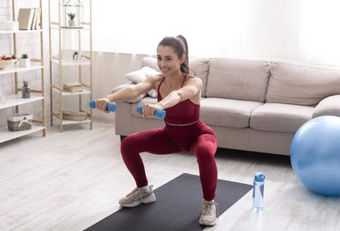 woman in red workout clothes doing dumbbell squats in her living room