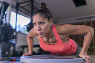 Woman doing body weight strength workout in home gym