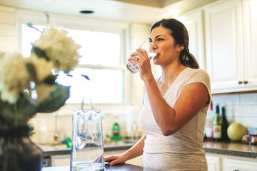 woman in her kitchen drinking a glass of water, as a natural remedy for sinus infections