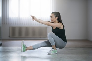 Woman doing a single-leg squat at home