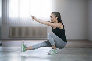 Woman doing a single-leg squat at home