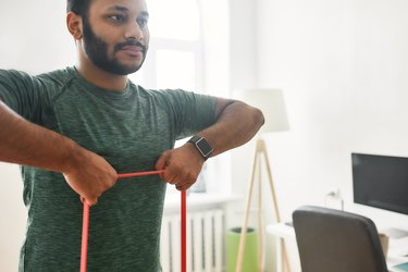 For strong arms. Cropped shot of young active man looking away, exercising with resistance band during morning workout at home. Sport, healthy lifestyle