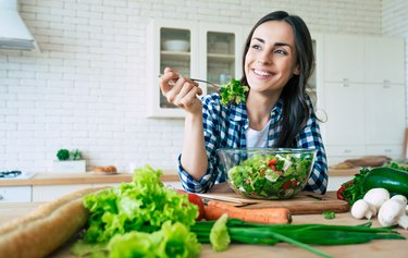 woman sitting in the kitchen and eating a large salad, as a natural remedy for heartburn