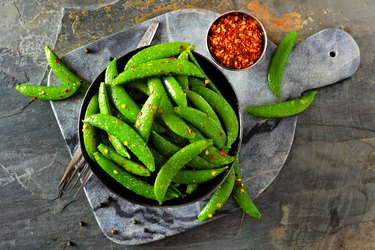 Healthy roasted sugar snap peas. Top view on a dark paddle board over slate