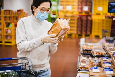 Woman wearing a face mask shopping for whole grain bread in the grocery store