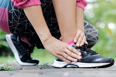 Running sport injury. Athletic woman runner touching foot in pain due to sprained ankle