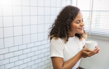 Portrait of young beautiful African american woman hands holding coffee cup morning winter time in white bedroom. Happy cheerful relaxing.  Wakeup cozy hygge routine university lifestyle concept.