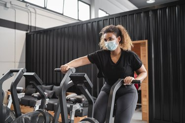 active woman wearing a face mask to exercise on a gym's stationary bike during the covid-19 pandemic